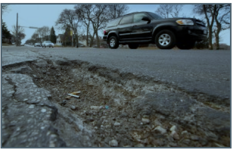 Traffic passes a pothole Thursday on Milwaukee's east side. 1000 Friends of Wisconsin and the Coalition for More Responsible Transportation is calling for money that is being used for an I94 expansion to instead be used for local roads. (Staff photo by Kevin Harnack)
